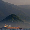 indonésie: The big and even bigger one: cargo ship and Mt. Agung.